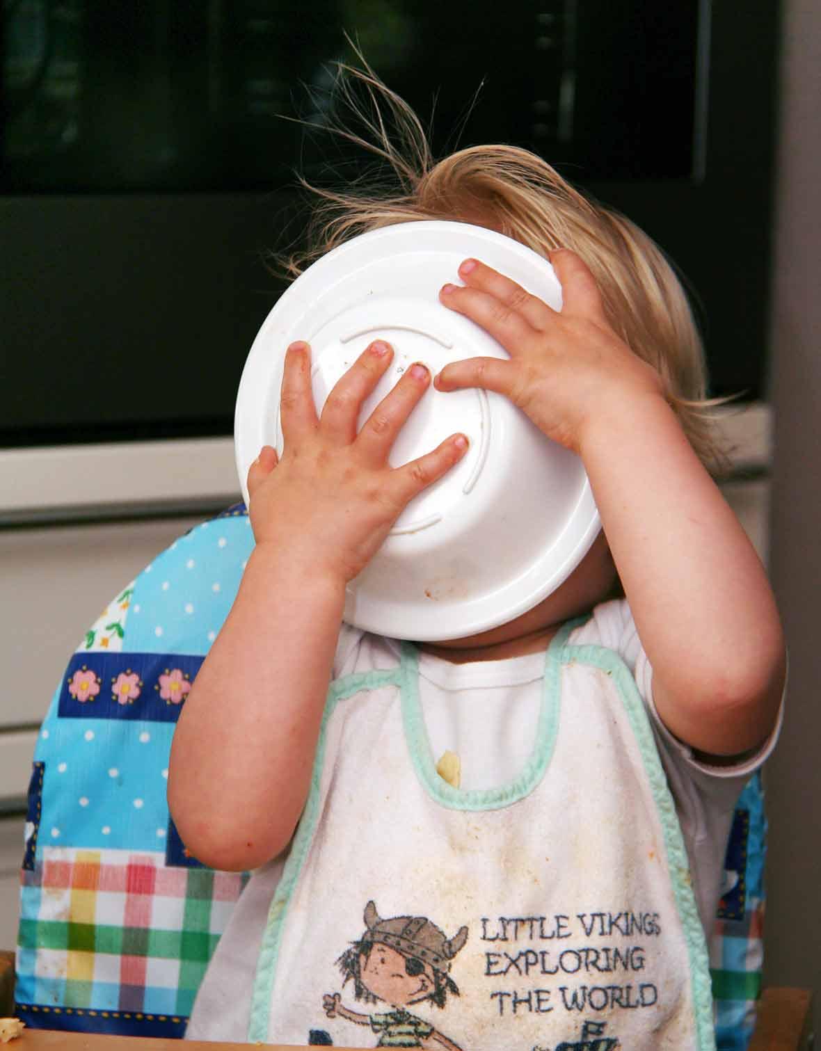 A kid in a high chair licking a bowl clean