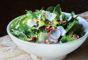 A bowl of a little gem salad--made up of little gem lettuce, radishes, shallots, walnuts, and walnut vinaigrette