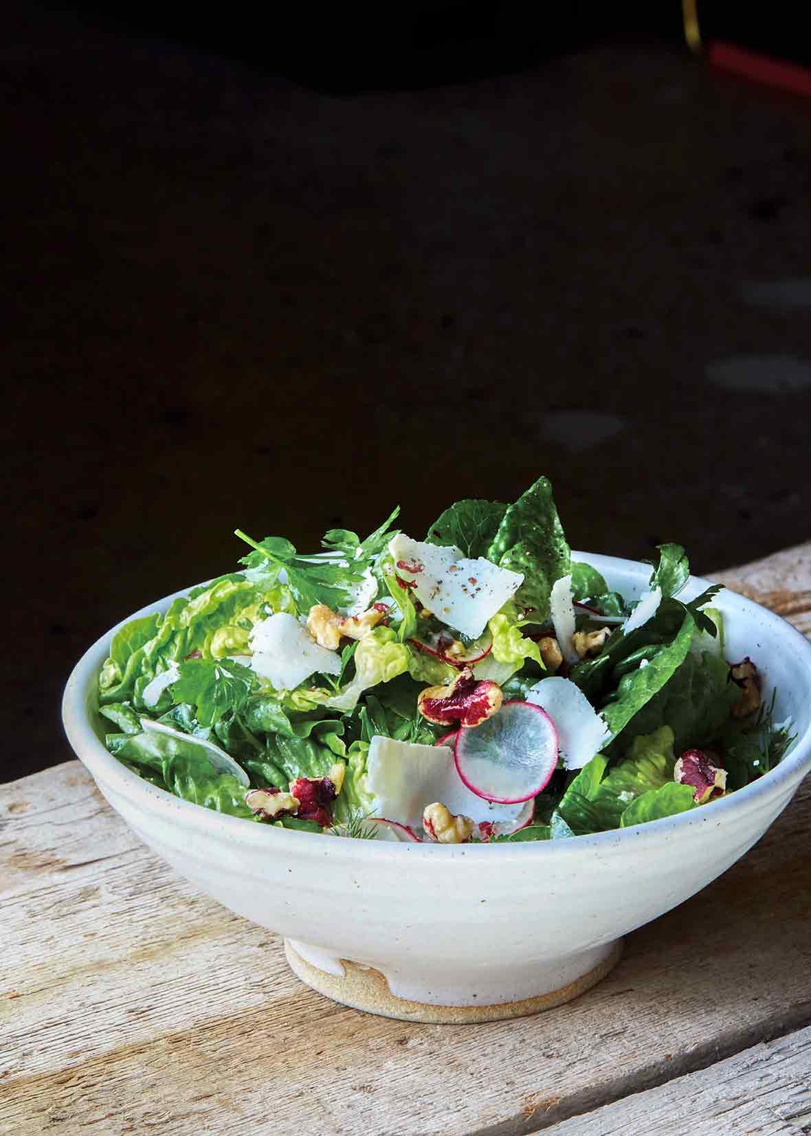 A bowl of a little gem salad--made up of little gem lettuce, radishes, shallots, walnuts, and walnut vinaigrette