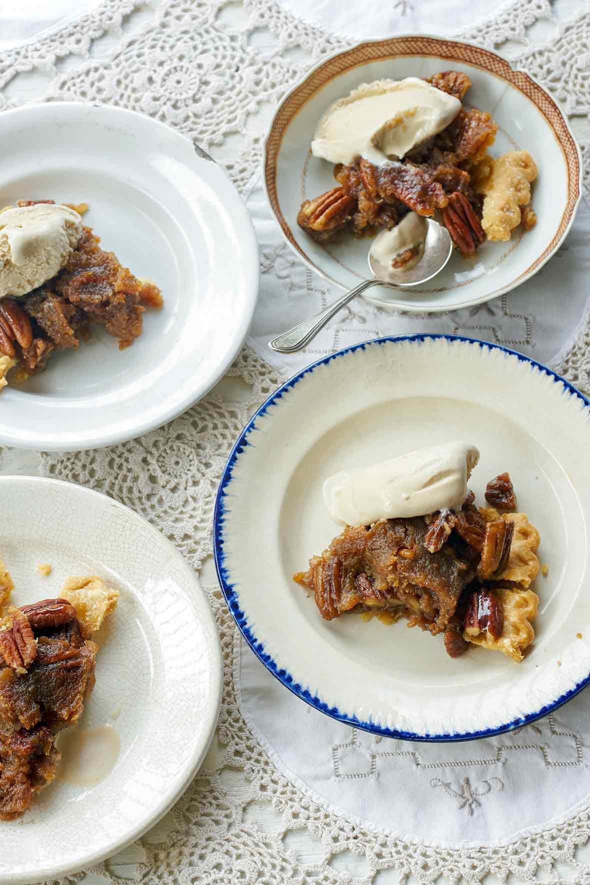 Four plates of rum pecan pie in a flaky crust, topped with whole pecans and vanilla ice cream