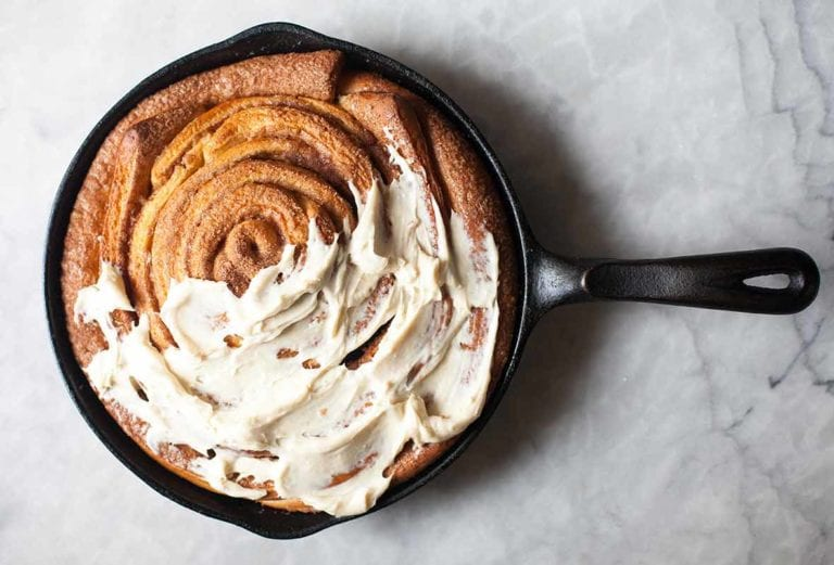 A giant skillet cinnamon roll in a black cast iron pan half cover with cream cheese icing