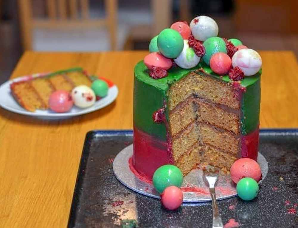 Three-layer vanilla paleo cake covered in red and green frosting and topped with candy globes