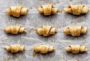 A baking sheet lined with parchment with 18 walnut rugelach cookies covered with brown sugar ready for the oven