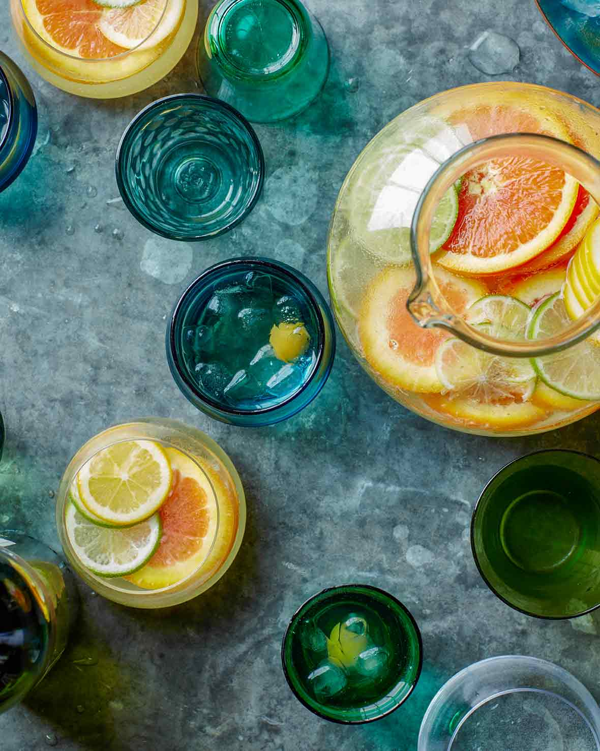 A pitcher and glasses of white sangria spritzer, filled with slices of lemons and oranges
