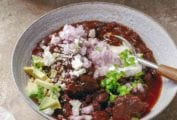 A white bowl filled with beef and black bean chili, topped with red onion, avocado, queso fresco, and diced jalapeno