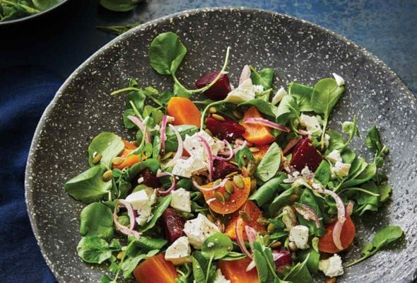 Gray speckled bowl of beet salad with feta and pumpkin seeds, along with spinach and sliced red onions