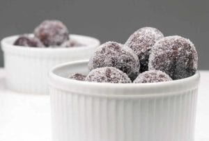 Two white ramekins with a pile of sugar-coated bourbon balls