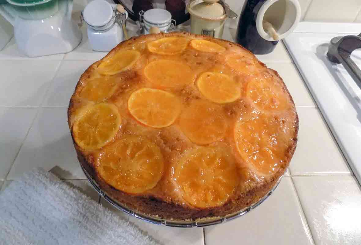 A clementine cake, topped with sliced clementines and a sweet glaze