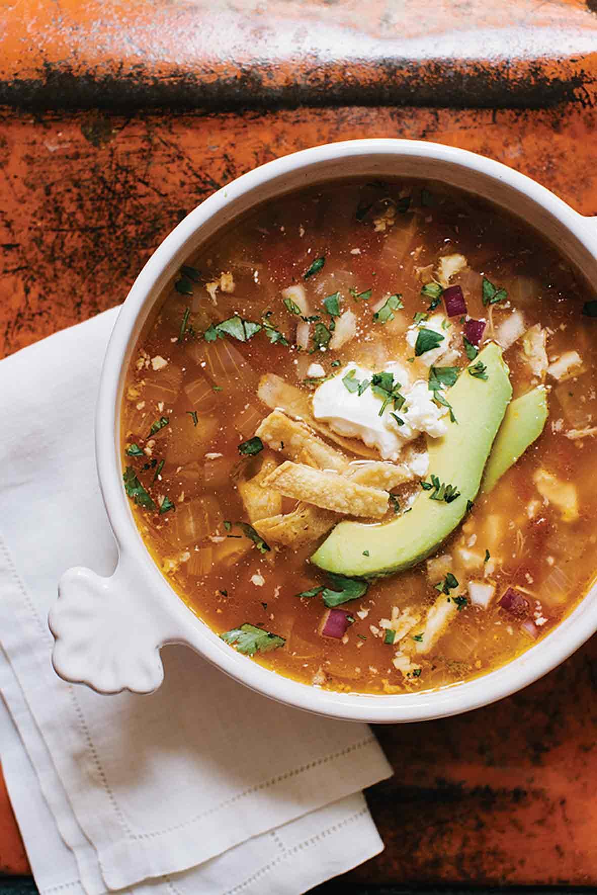 A bowl of easy chicken tortilla soup, with chicken, avocado, tortilla strips, and sour cream