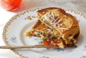 A grilled cheese sandwich with peppers is cut in half and stacked on a china plate with a jar of pepper jelly on the side