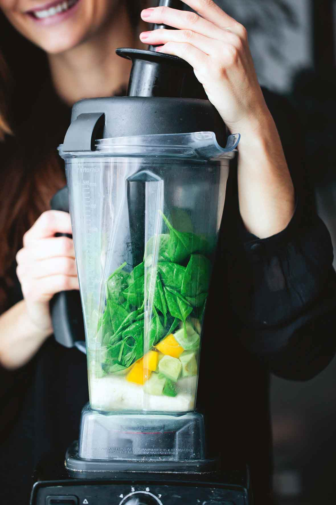 A woman with a Vitamix filled with spinach, mango, and milk