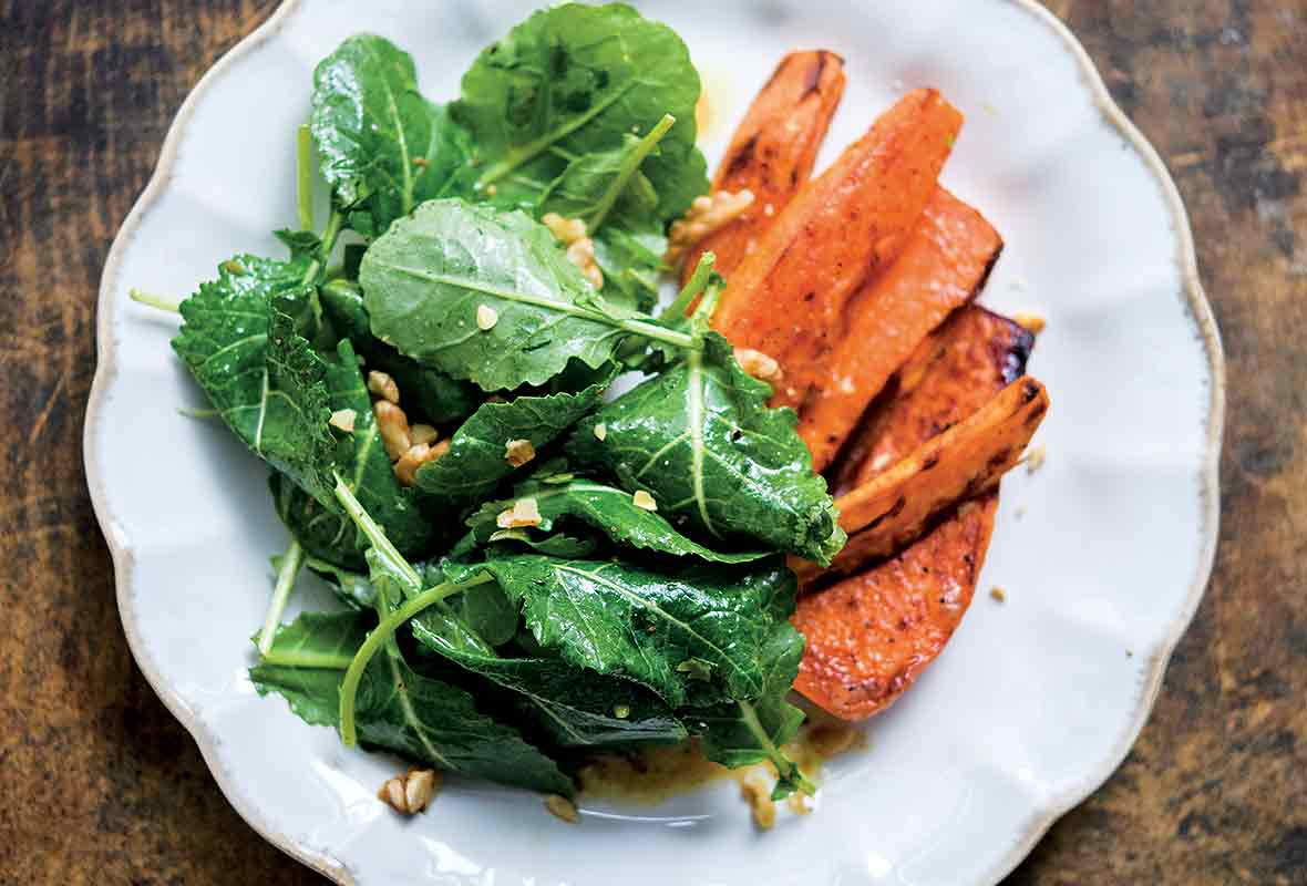 white plate of kale miso salad with roasted sweet potatoes on the side