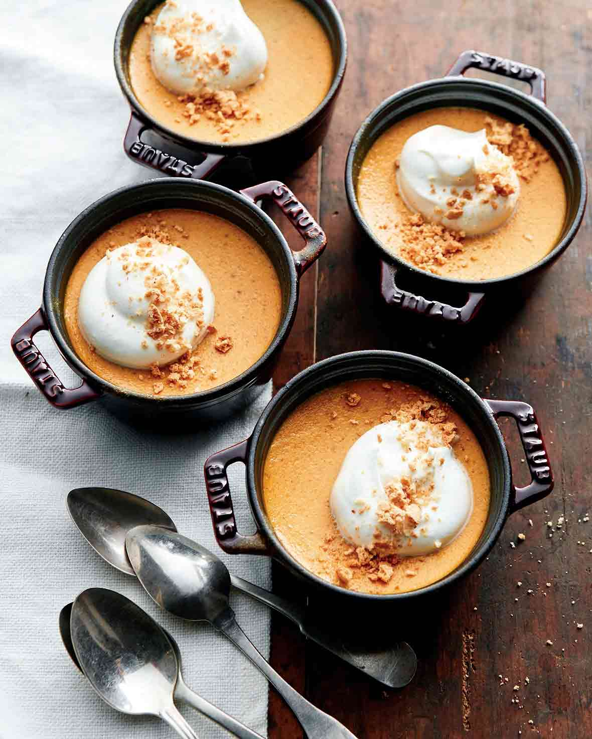 Four small crocks of pumpkin pots de creme--pumpkin pudding topped with crumbled cookie and whipped cream