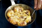 A man with a skilet of Portuguese punched potatoes, caramelized onions, cheese, called batatas a murro in Portuguese