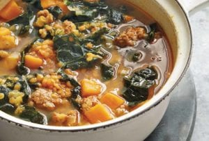 Bowl of red lentil soup with kale and chorizo, sweet potatoes, and onions