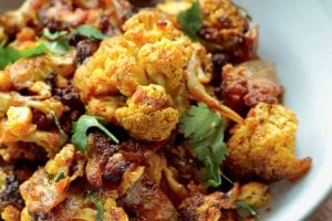 A bowl of roasted curried cauliflower mixed with onions and topped with cilantro