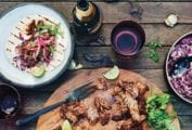 A wooden platter with a braised beef shank, cilantro, lime, and pickled onions