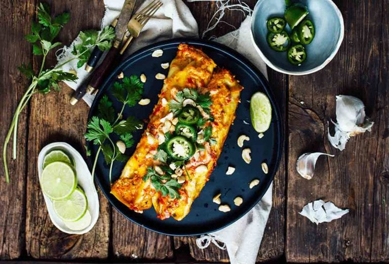 A casserole dish of sweet potato enchiladas with a place with two enchiladas, lime, jalapenos, and sauce