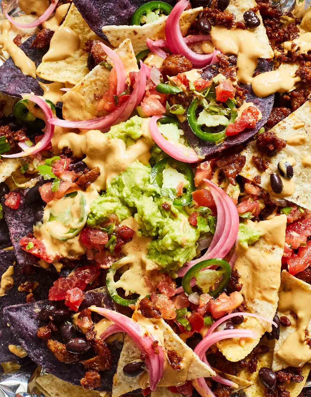 A close up of vegan nachos made with seitan, plus a sour lime cream, cashew, pickled red onions, avocado, jalapeño, and cilantro