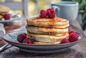A stack of four vegan pancakes on a plate, dripping with maple syrup and topped with raspberries