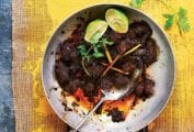 A stainless steel skillet filled with beef rendang and topped with two lime halves, lemongrass, and cilantro