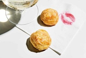 Two best gougeres on a cocktail napkin with a lipstick print on it and a glass of Champagne
