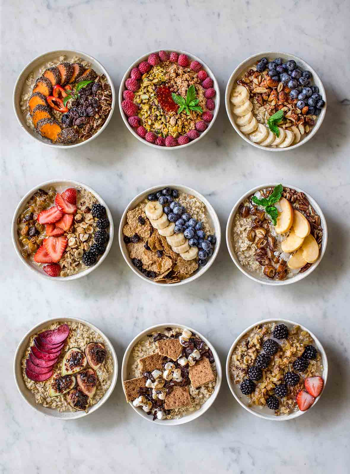 Nine bowls of oatmeal with different toppings created from an oatmeal bar