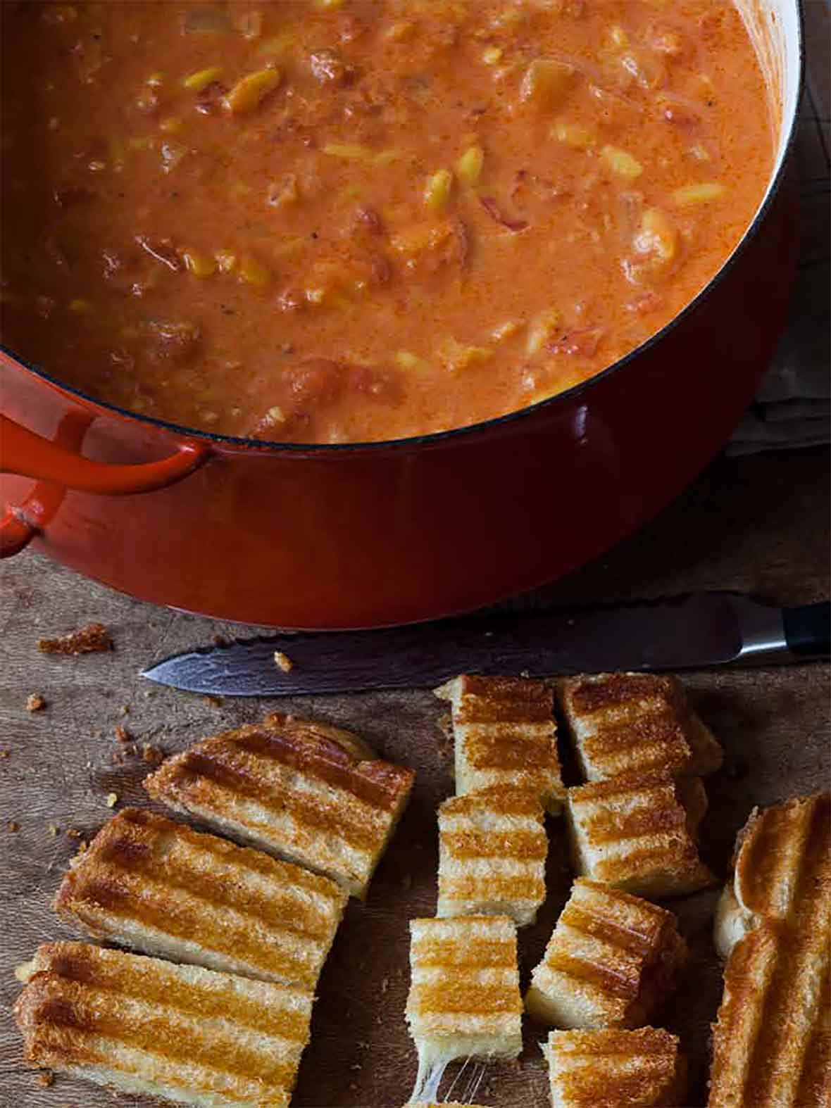 A large pot of easy tomato soup with a grilled cheese sandwich being cut into croutons beside it.
