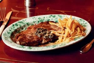 A green and white patterned plate filled with entrecôte à l'anchoïade and a pile of French fries