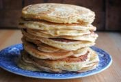 A blue plate piled with a stack of griddle cakes