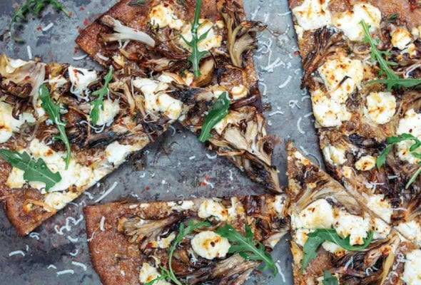 A mushroom and goat cheese pizza topped with dandelion leaves cut into six slices
