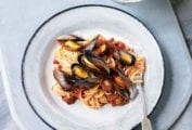 A white plate topped with linguine and mussels in a red dress