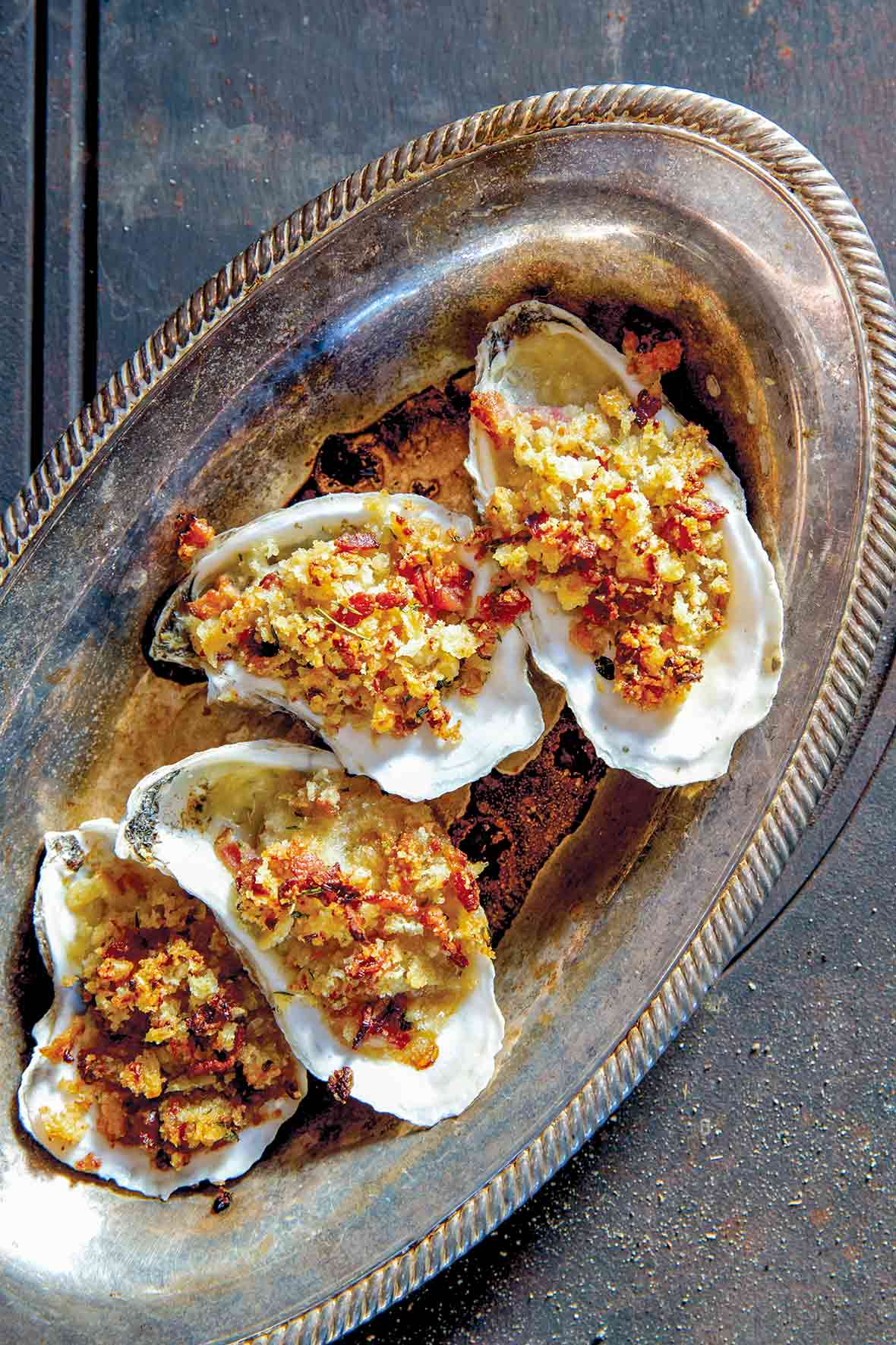 A tray of oysters Rockefeller with bacon--baked oysters topped with bread crumbs, bacon, and butter