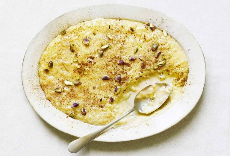 A white serving platter filled with Portuguese rice pudding and topped with toasted pistachios and cinnamon