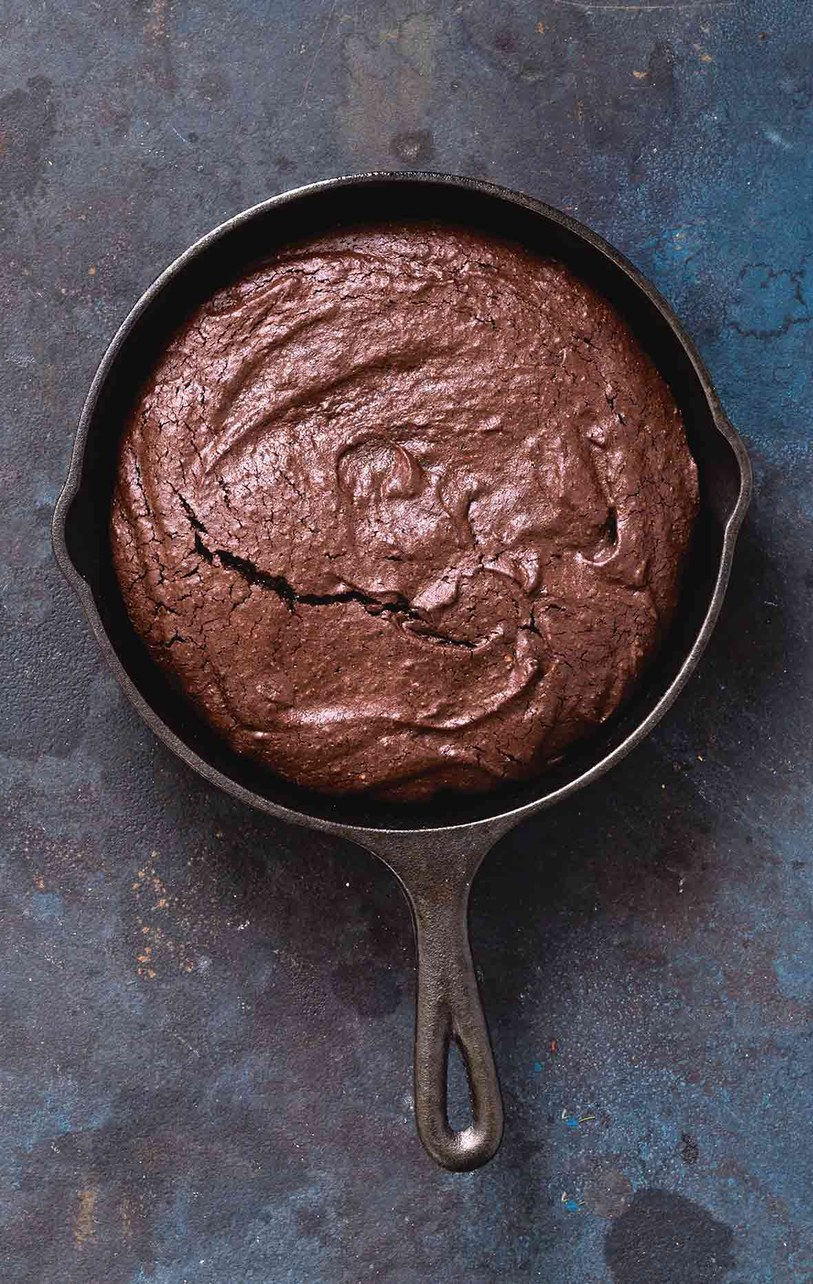 A cast-iron skillet filled with chocolate brownie