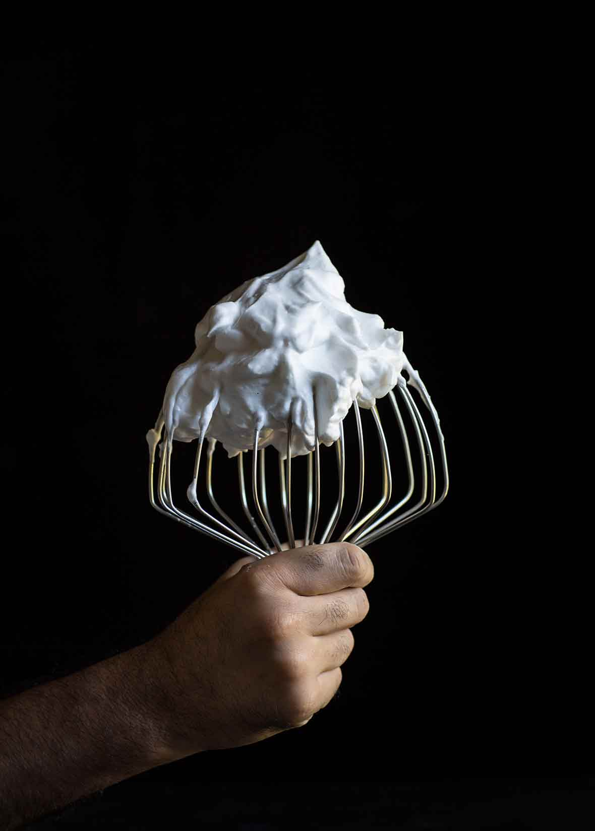 A hand holding a stand-mixer whisk covered in vegan meringue