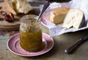 A jar of celery marmalade with a spoon in it and several types of cheese in the background