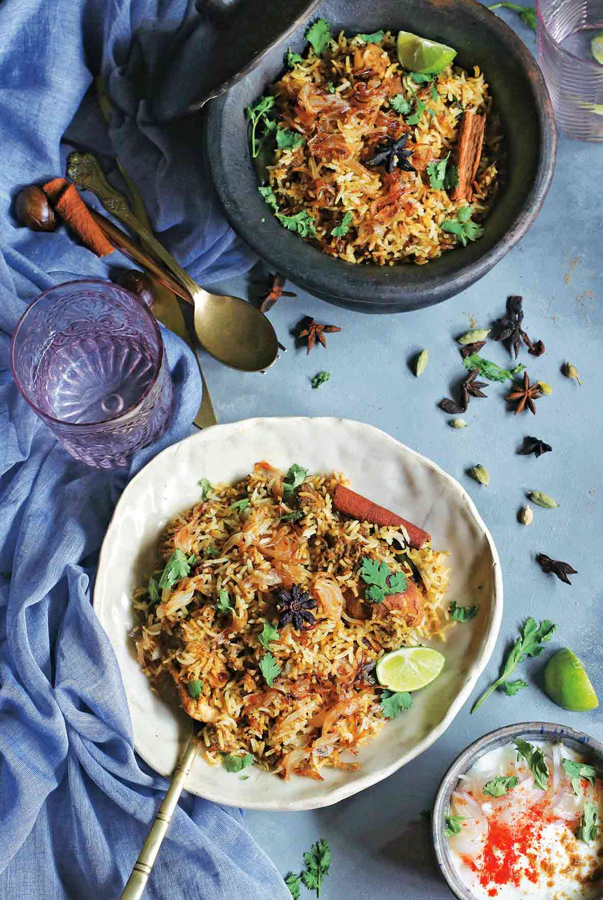 Two bowls filled with chicken biriyani on a blue cloth