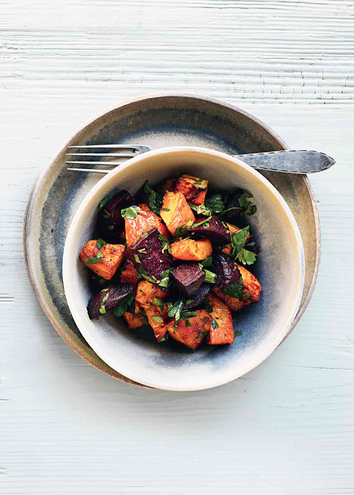 An earthenware bowl filled with curried butternut squash and beets, on a plate with a fork resting beside the bowl