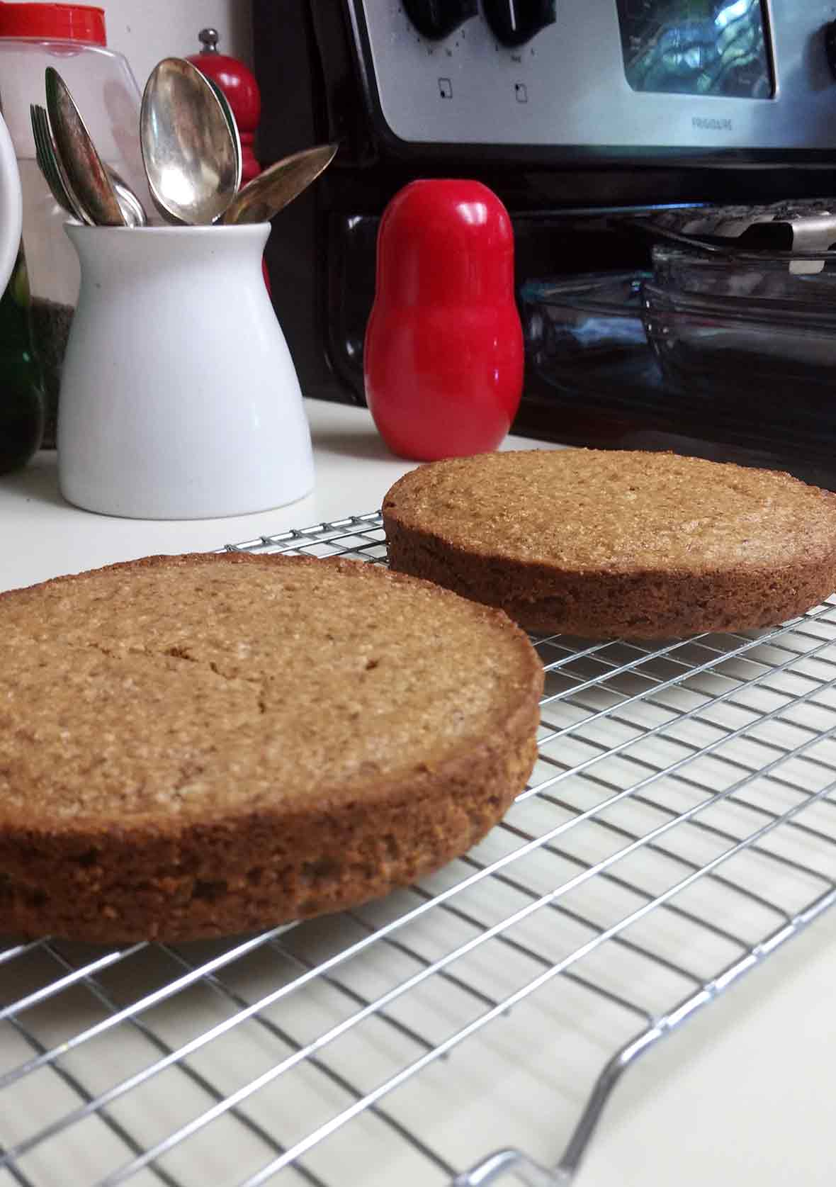 Two flourless almond cakes on a cooling rack on a kitchen counter