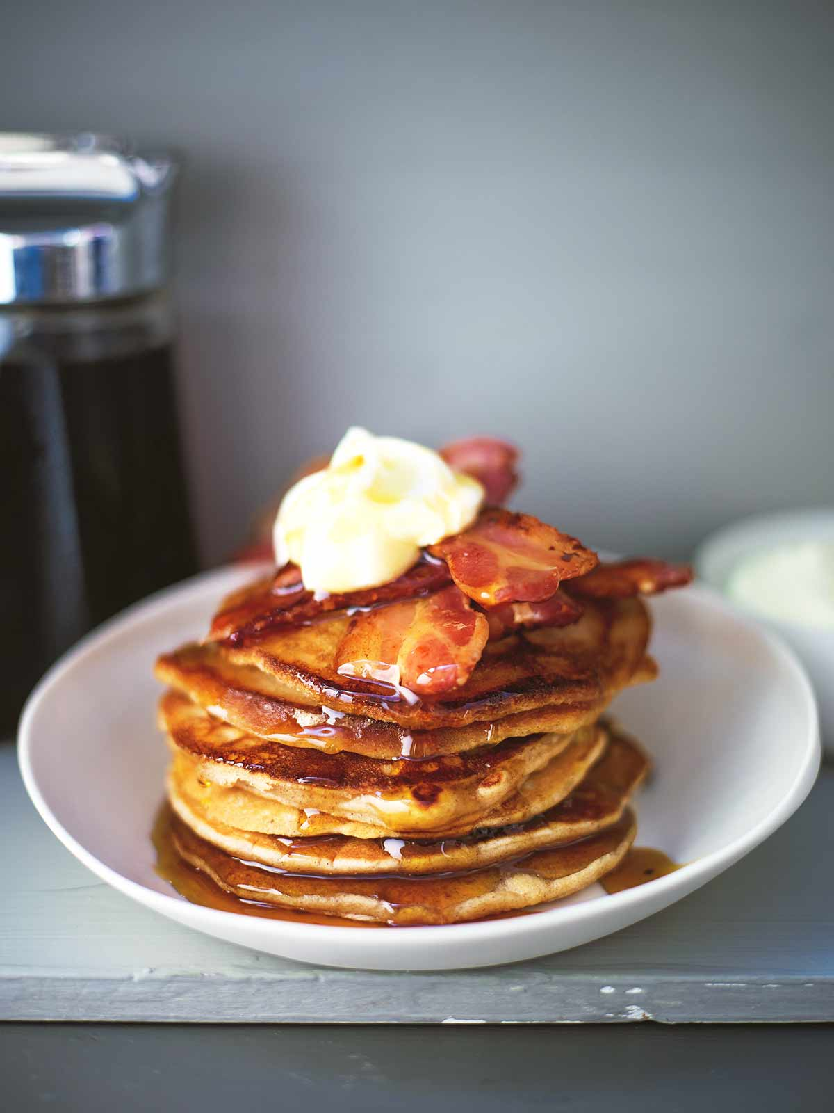 A stack of easy gingerbread pancakes topped with bacon, maple syrup, and creme fraiche in a white bowl.
