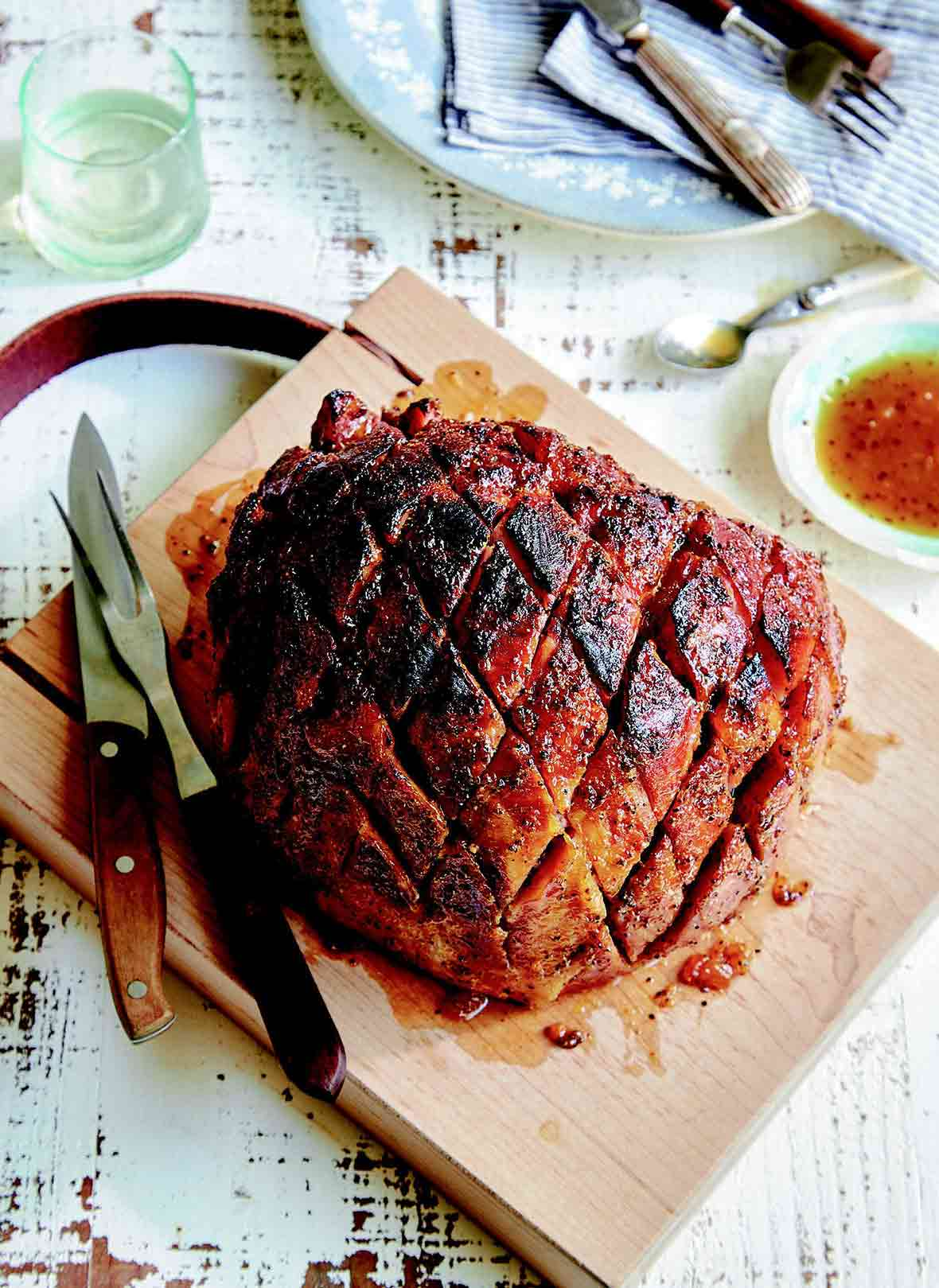 A fully cooked ham with ginger peach glaze on a carving board