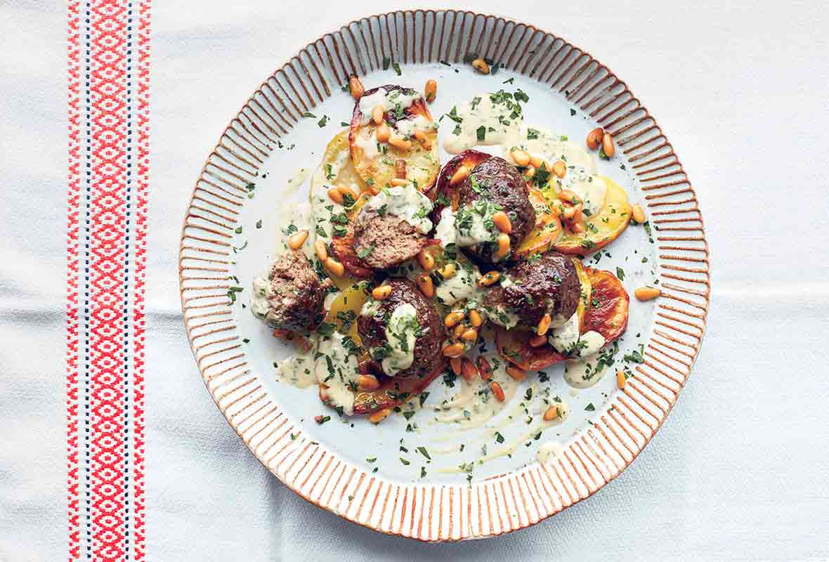 A white plate with striped edges filled with potatoes and lamb meatballs with tahini