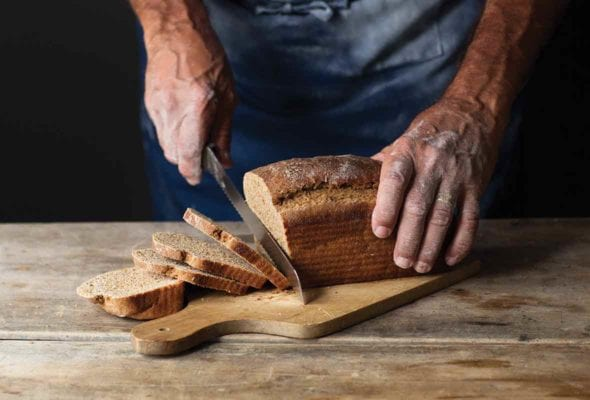 A man cutting a loaf of milk rye bread on a wooden board