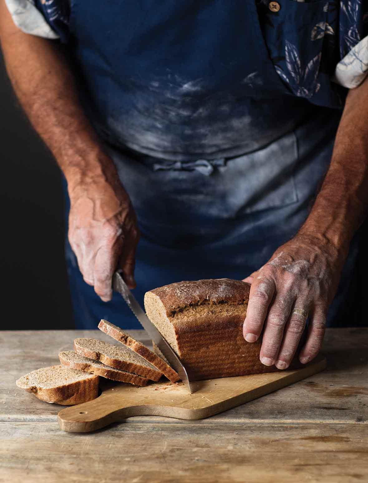 A man cutting a loaf of milk rye bread on a wooden board