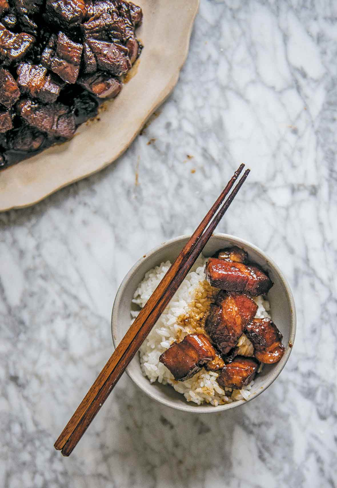 A bowl of rice topped with red cooked pork and a pair of chopsticks resting on the bowl. A plate of red cooked pork on the side