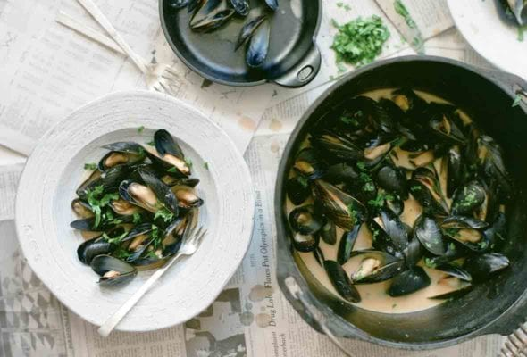 A pail and a white bowl filled with red curry mussels, as well as a bowl of discarded mussel shells