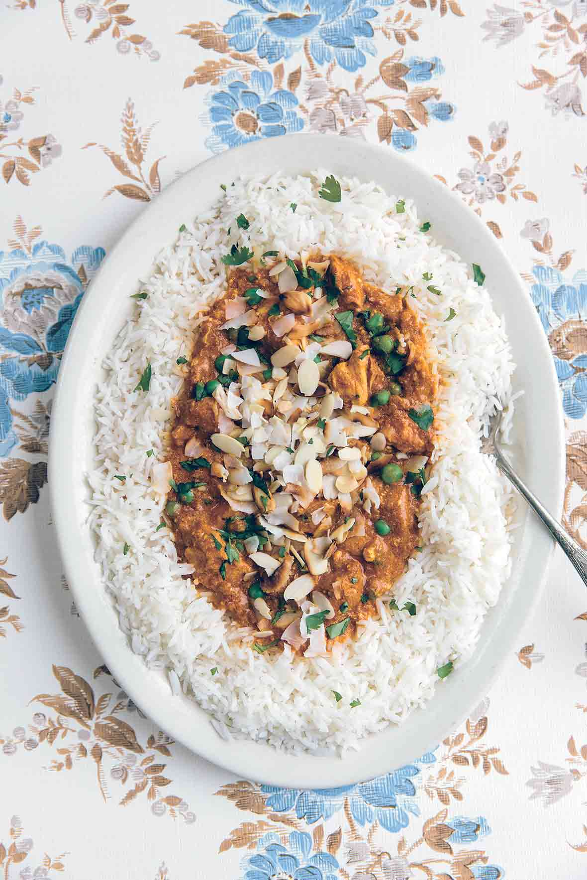 A white serving platter filled with slow cooker Indian butter chicken on a bed of basmati rice, topped with almonds and coconut