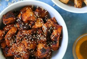 A white bowl filled with spicy Korean chicken and sprinkled with sesame seeds
