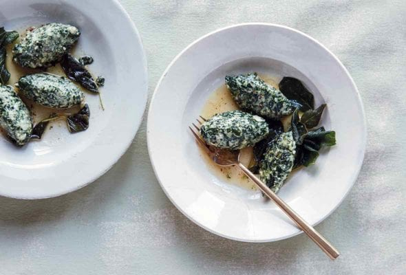 Two bowls, each with three spinach and ricotta gnudi and several fried sage leaves